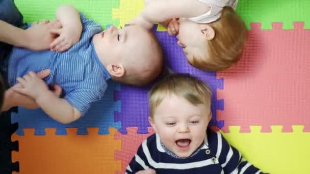 Pohled na kojence a malé děti ležící na rohoži v dětském divadle Polechtané matkami a smíchem