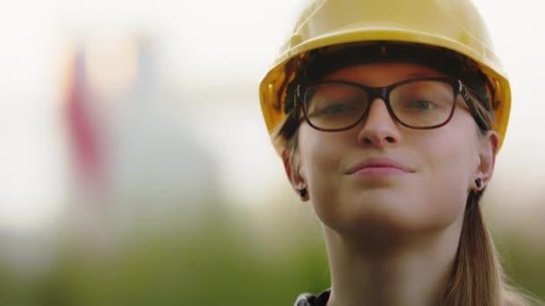 Porträt einer jungen kaukasischen Bauingenieurin, die mit dem Kopf nickt. Frau mit Brille und gelbem Hut