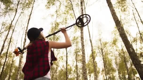Visszapillantás a fiatal nőre, amint fémdetektort emel az erdőben. Lassú mozgás fénymásoló térrel