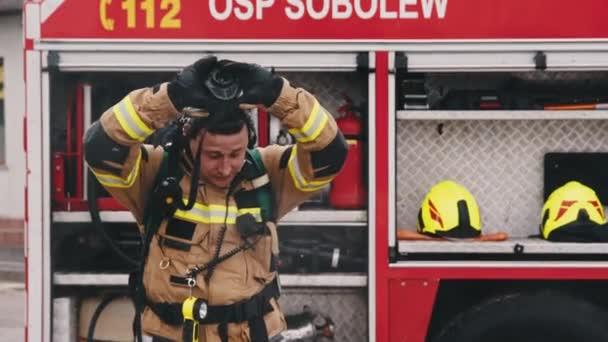 Varšava, Polsko, 05-30-2020 - OSP SOBOLEW, firefigter demontáž masky před hasičským sborem
