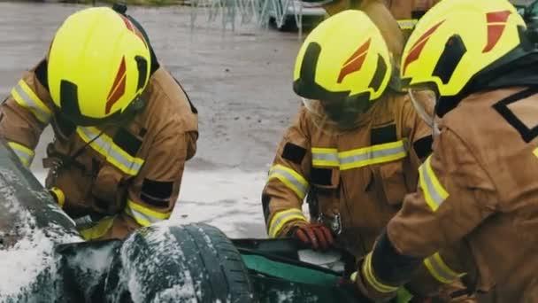 Tým hasičů se snaží otevřít dveře od auta, aby zachránili osobu zapojenou do nehody. Zpomalený pohyb