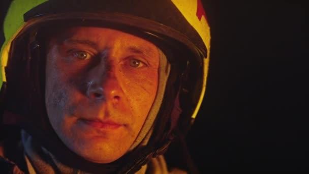 Portrét hasiče v akci mluvícího na vysílačce. Ohnivý odraz na přilbě