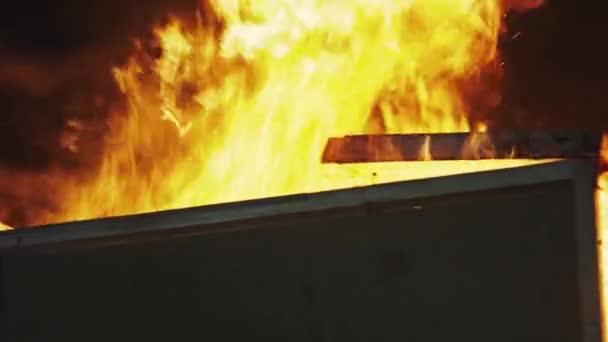 Hořící dům a hasič přijíždějí zachránit. Statečný hasič se pomalu přibližuje k ohni.