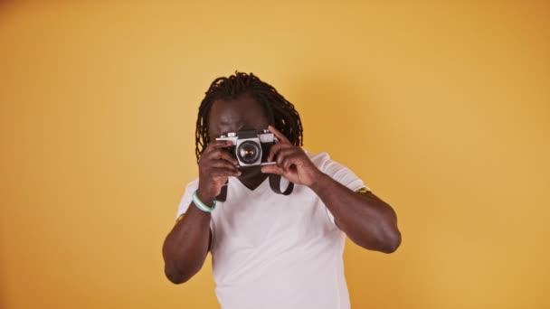 Portrét Afričana držícího v ruce kameru. Izolováno na oranžovém pozadí