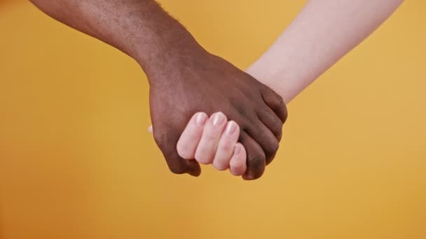 black and white hands holding together isolated on the orange background. Close up