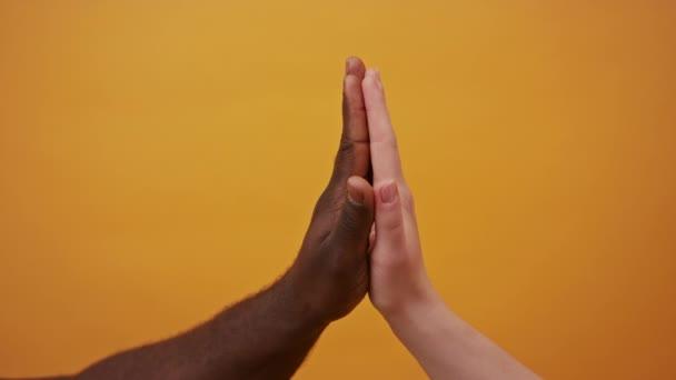 černé a bílé ruce drží pohromadě izolované na oranžovém pozadí. Zavřít