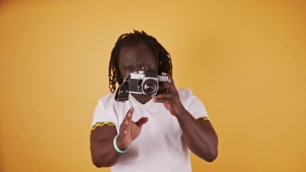 Portrét afrického muže s copánkovým sluchem a bílou košilí držícího v ruce kameru. Izolováno na oranžovém pozadí
