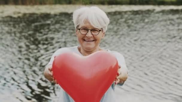Seniorin mit herzförmigem Ballon in der Nähe des Flusses. Konzept Liebe und Fürsorge