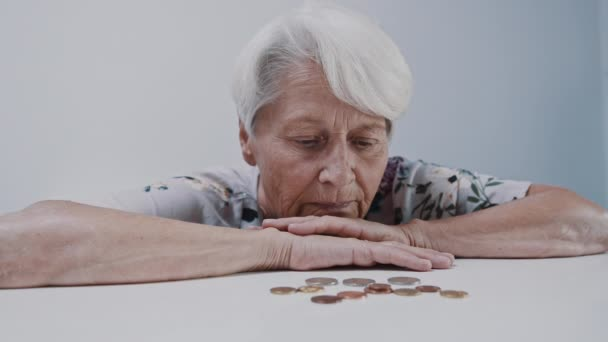 Eine unglückliche alte Frau schüttelt vor Münzen den Kopf über ihre Hände. Die Ersparnisse gehen aus, die Verweigerung