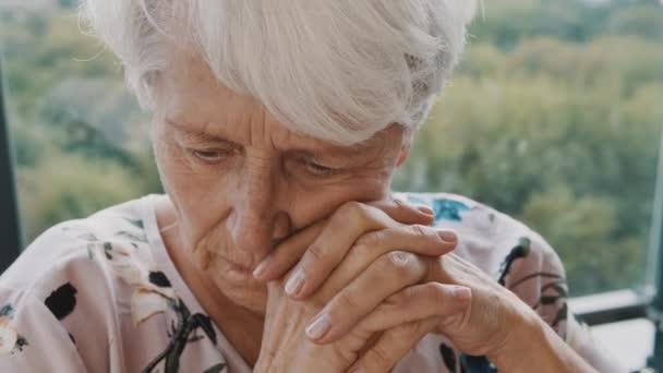 Starší běloška v pečovatelském domě, se smutkem v očích, samovolná izolace v důsledku celosvětové pandemie koronaviru COVID-19