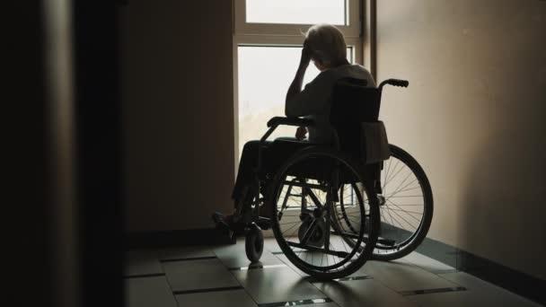 Einsame Seniorin blickt aus dem Fenster des Pflegeheims. Psychische Gesundheit während der Quarantäne beeinträchtigt