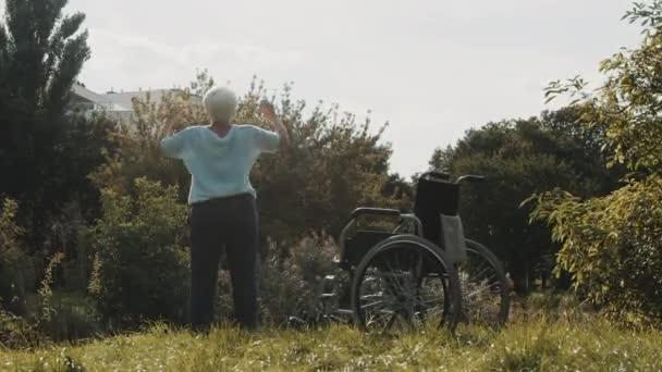 Recovery Konzept. Alte Frau übt im Park vor dem Rollstuhl