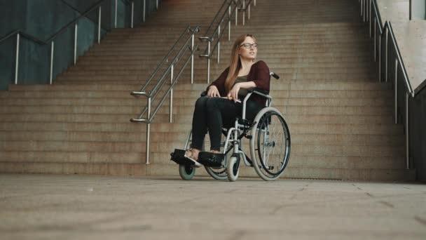 Hoffnungslose junge Frau im Rollstuhl vor der unzugänglichen Treppe.