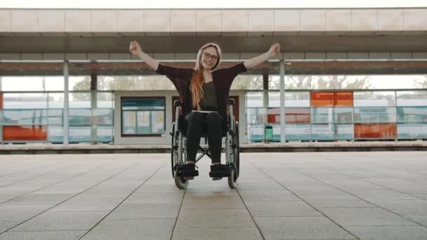 Glückliche junge selbstständige Behinderte auf dem Bahnhof
