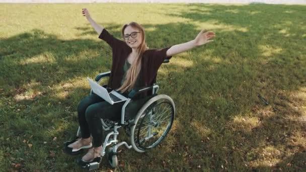 glückliche junge behinderte Kaukasierin im Rollstuhl, die mit Laptop und Smartphone in der Natur ruht
