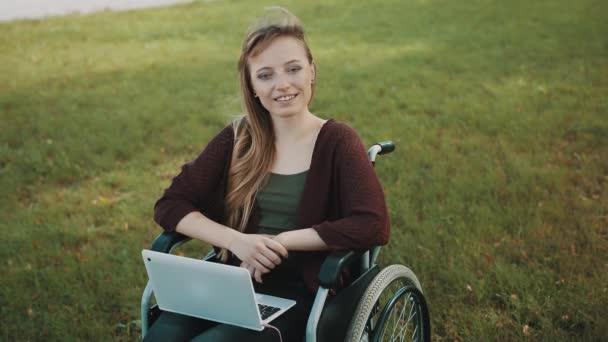 Remote-Arbeitskonzept. Junge behinderte Frau im Rollstuhl mit Smartphone und Laptop