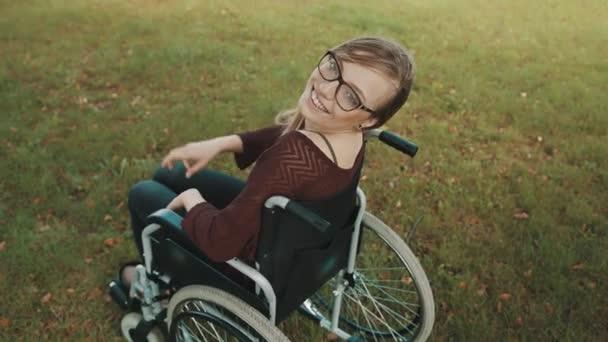 Schöne behinderte kaukasische Frau, die im Park über die Schulter schaut, Friedensgeste