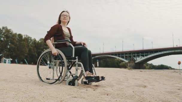 Junge Frau im Rollstuhl an der sandigen Flussküste genießt die Herbstbrise
