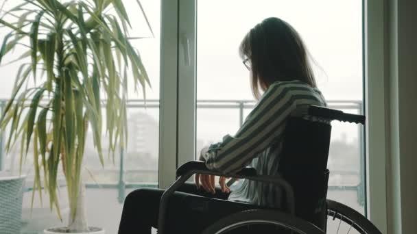 Junge depressive einsame behinderte Frau blickt durch die Balkontüren