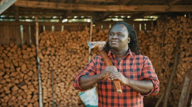 African man with the axe standing in front of stack of cutted timber for winter