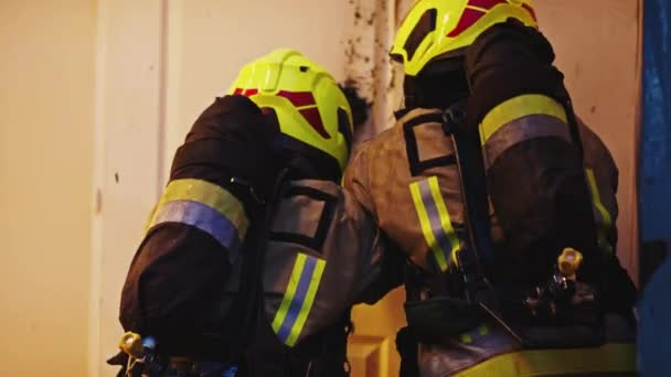 Hasiči rozbíjejí hořící domovní dveře