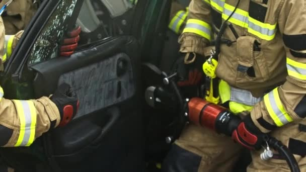 Hasiči řežou dveře auta, aby zachránili oběti autonehody