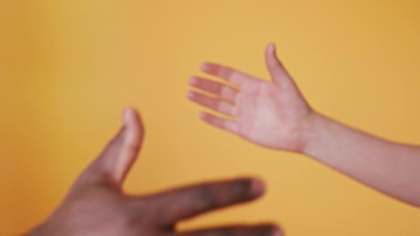 Černobílé ruce drží pohromadě, plácneme si na oranžovém pozadí. Zavřít