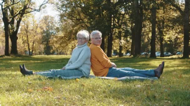 Starší pár si užívá romantického podzimního dne v parku, sedí zády k sobě a obrací hlavy ke kameře