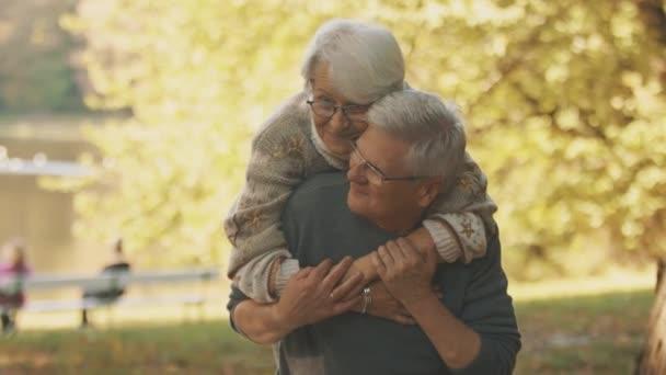 Šťastný starý pár objímající se v parku. Starší muž flirtuje se starší ženou. Romantika ve stáří tanec na podzim den