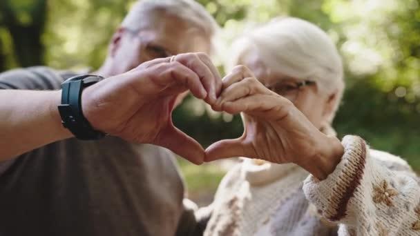 Starší pár ve výslužbě si dělá srdce rukama. Selektivní zaměření