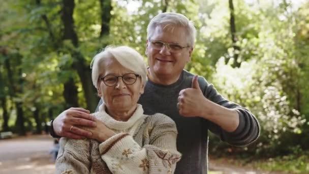 Šťastný starý pár objímající se v parku. Starší muž flirtuje se starší ženou. Palce nahoru