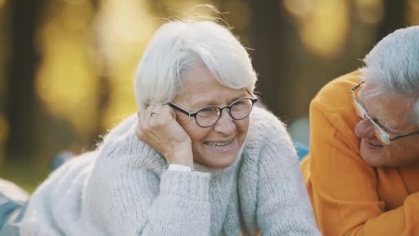 Romantika ve stáří. Pár v důchodu si užívá podzimní piknik. Leželi na černé noze a dívali se jeden na druhého