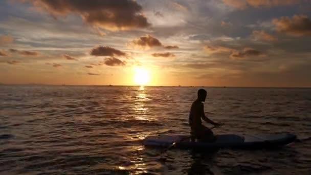 Mladý chlapec dělá pádlo surfovat, zatímco slunce zapadá na moře