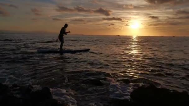 Junge beim Paddelsurfen, während die Sonne auf dem Meer untergeht