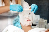 kosmetička aplikuje masku na žena