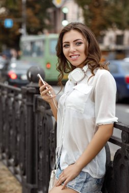 beautiful smiling young woman with headphones uses smartphone in city