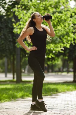 woman drinks water after running