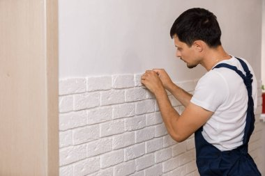 Professional Builder gluing decorative tile on wall.