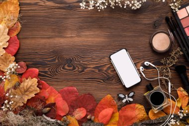 female accessories Set. autumn leaves, smartphone and earphones on wooden background