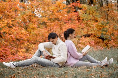 Happy couple in love sitting in beautiful autumn park and reading books stock vector