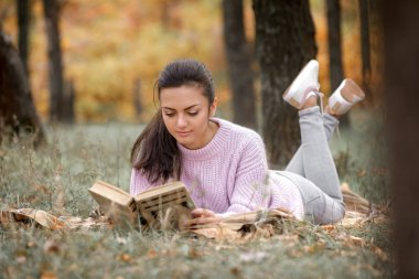 Happy young woman sitting in beautiful autumn park and reading book stock vector