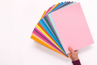 woman hand holding sheets of different colored paper.