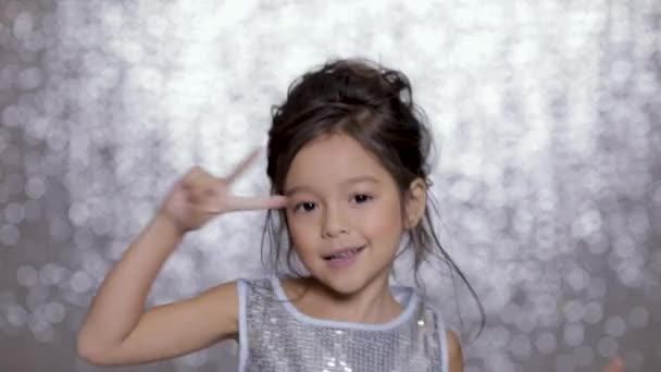 beautiful smiling little child girl in a silver dress dancing on background of silver bokeh.
