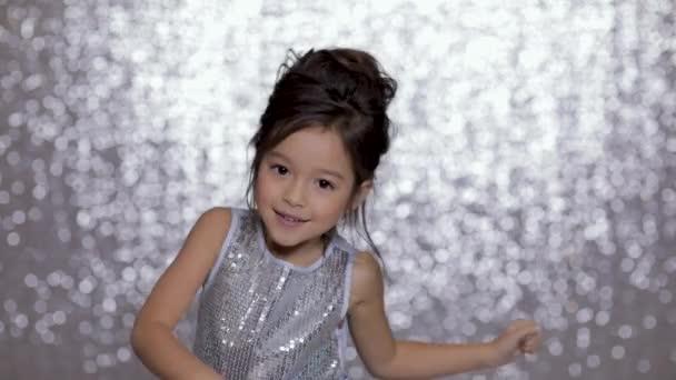 niedlich glücklich kleines Mädchen Kind in einem silbernen Kleid tanzen auf dem Hintergrund der silbernen Bokeh.