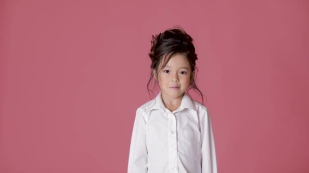 roztomilá holčička dítě v bílé košili ukazuje různé emoce na růžovém pozadí.