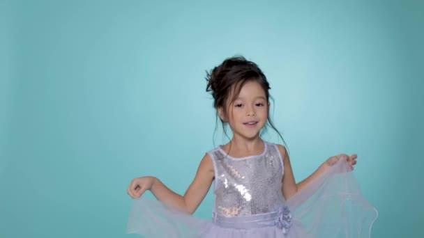 schönes kleines Mädchen in silbernem Kleid, das auf blauem Hintergrund tanzt.