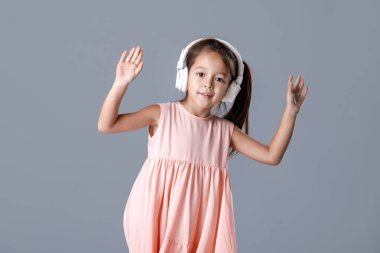 little girl in dress and headphones listens to music and dances