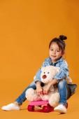Photo Stylish little child girl with skateboard in denim on orange background