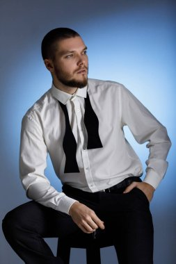 young bearded man in a white shirt and bow tie
