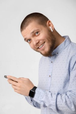 bearded businessman uses wireless headphones and smartphone